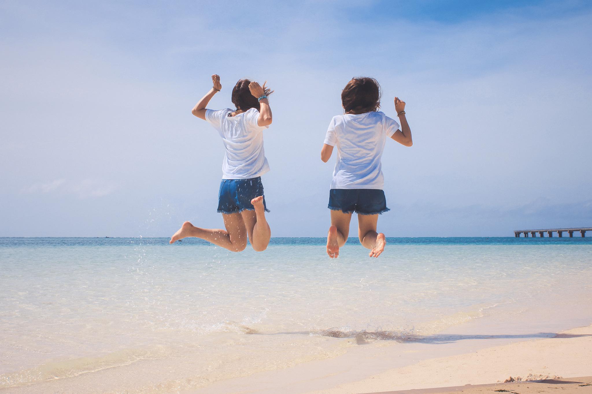 海を背景にジャンプする女性